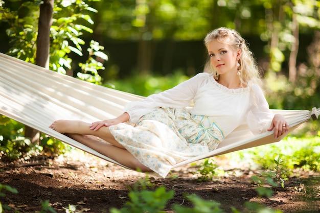 Dama siedzi na huśtawce hamak drzewo.