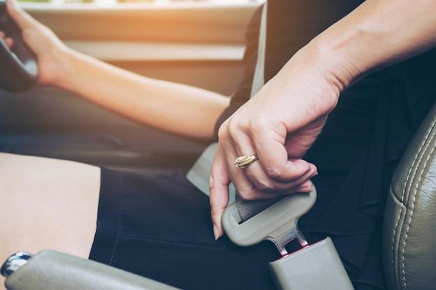 Dama stawia samochodowego pas bezpieczeństwa przed jeżdżeniem, zamyka up przy pasową klamrą, bezpieczny prowadnikowy pojęcie
