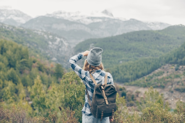 Dama stoi i robi zdjęcia górom w przyrodzie w szary kapelusz i dżinsy w ciągu dnia
