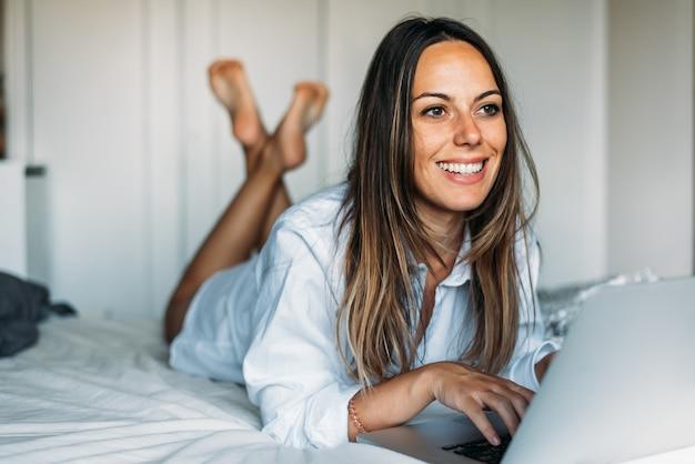 Dama uśmiecha się i pisze na klawiaturze laptopa podczas relaksu na łóżku