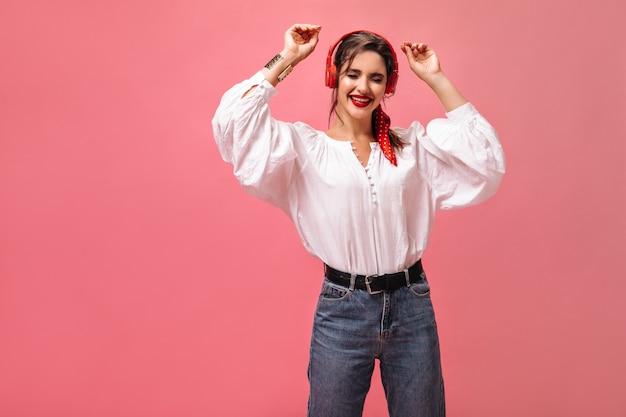 Dama w białej bluzce i dżinsach tańczy i słucha muzyki w słuchawkach. stylowa pani iw modnym stroju pozowanie na różowym tle.