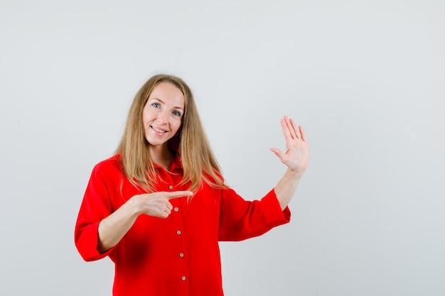Dama w czerwonej koszuli wskazująca na bok, pokazująca dłoń i wyglądająca wesoło,