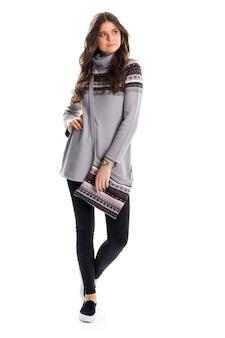 Dama w długim szarym swetrze. czarne slipy i spodnie. codzienna odzież na jesień. strój z modnym obuwiem.