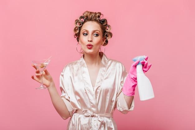 Dama w jedwabnej szacie gwiżdże, trzymając detergent i kieliszek martini na różowej ścianie