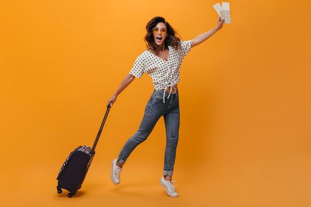 Dama w świetnym nastroju skacze na pomarańczowym tle z biletami i walizką. szczęśliwa kobieta z falistymi krótkimi włosami w okularach przeciwsłonecznych w trampkach dobrze się bawić.