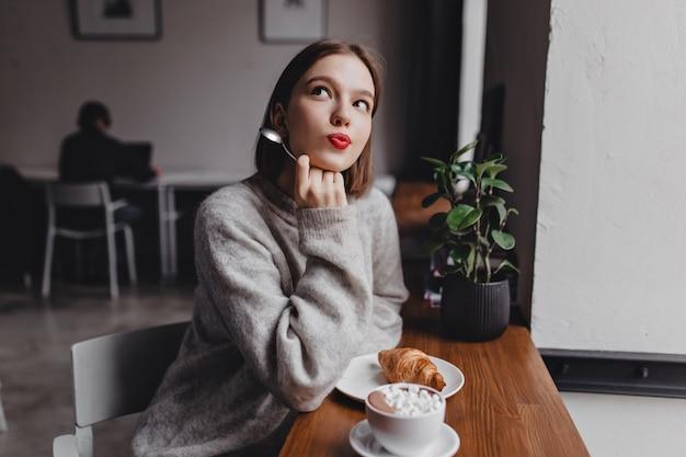 Dama w szarym, oversizowym stroju pozuje rozmarzona w kawiarni. portret młodej dziewczyny przy stole z rogalikiem i cappuccino.