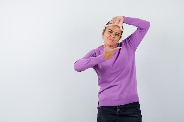 Dama w wełnianej bluzce robi gest łuski i wygląda radośnie