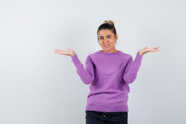 Dama w wełnianej bluzce robi gest łuski i wygląda wesoło