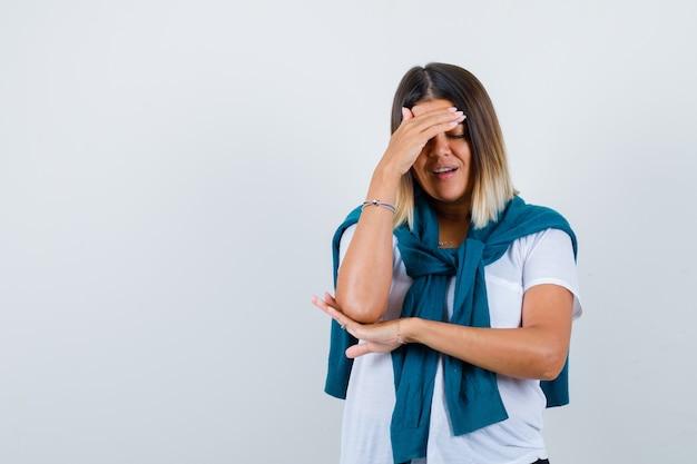 Dama w wiązanym swetrze trzymająca rękę nad głową w białej koszulce i wyglądająca na zmęczoną, widok z przodu.