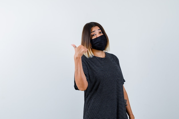 Dama wskazująca w lewo z kciukiem w czarnej sukience, masce medycznej i wyglądająca na niezdecydowaną, widok z przodu.