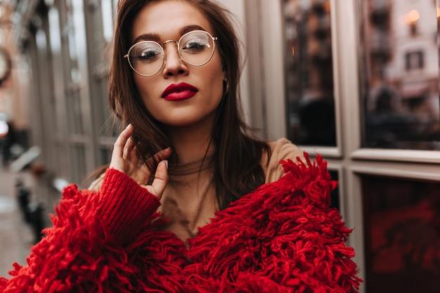 Dama z bordową szminką dotyka swoich ciemnych włosów. kobieta w świetnym nastroju ubrana w czerwoną wełnianą kurtkę ciesząca się ciepłym, jesiennym dniem na dworze.