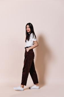 Dama z długimi włosami ubrana w brązowe spodnie pozuje na beżowej ścianie