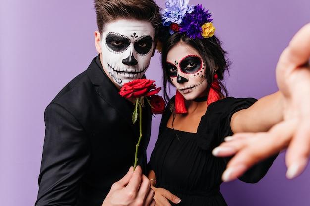 Dama z koroną róż i czerwonymi kolczykami robi selfie, a młody mężczyzna ze sztuką twarzy na halloween trzyma różę.