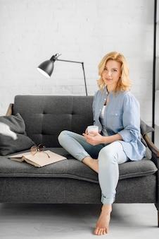 Dama z książką i filiżanką kawy na czarnej kanapie