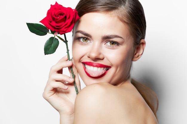 Dama z różą pokazuje język uśmiech nagich ramion