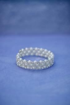 Damska bransoletka jubilerska w białych perłowych koralikach dla panny młodej z bliska na niebieskim tle