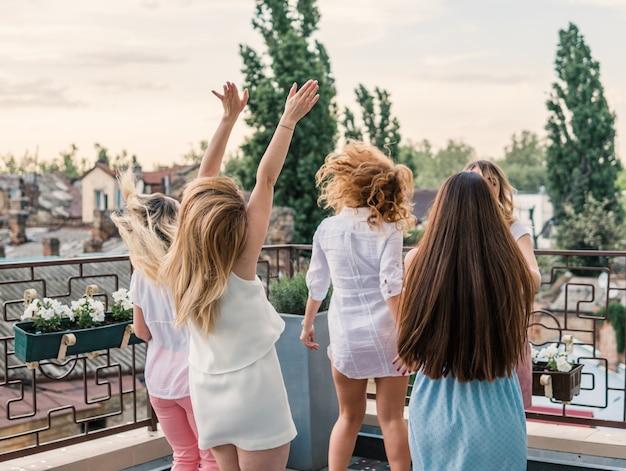 Damska impreza. piękne kobiety przyjaciół na balkonie zabawy na wieczór panieński. tańczą na dachu