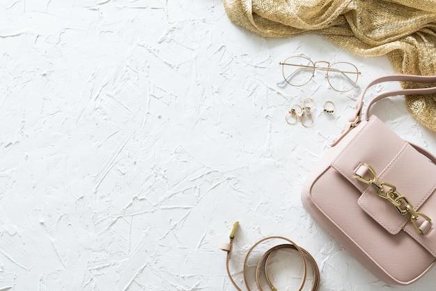 Damska złota i różowa moda płaskie akcesoria lay na tle betonu
