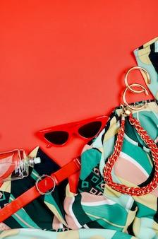 Damski letni czerwono-zielony zestaw ubrań i akcesoriów na pomarańczowym tle widok z góry