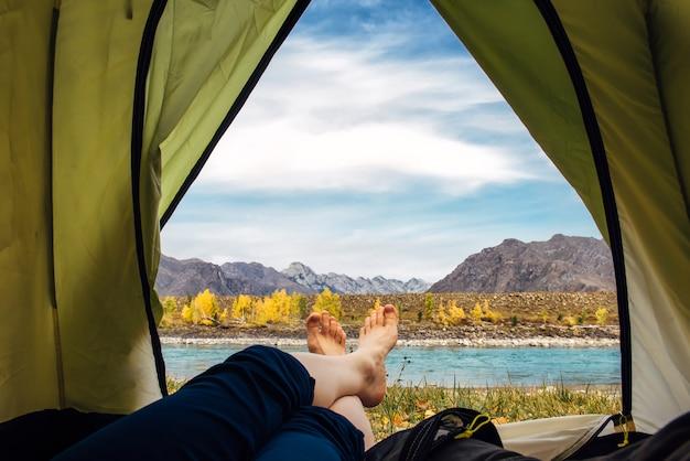Damskie boso w niebieskich spodniach skrzyżowane na skraju zielonego namiotu turystycznego.