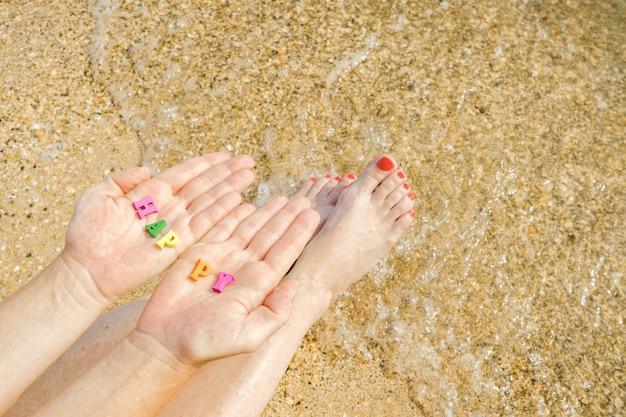 Damskie dłonie i stopy na tle morskiego piasku w dłoniach napis szczęście