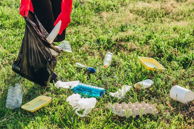 Damskie dłonie w czerwone gumowe rękawiczki. kobieta zbiera śmieci w torbie. wolontariusz zmiatania śmieci w lecie parku. miła postępowa kobieta stara się pomagać środowisku