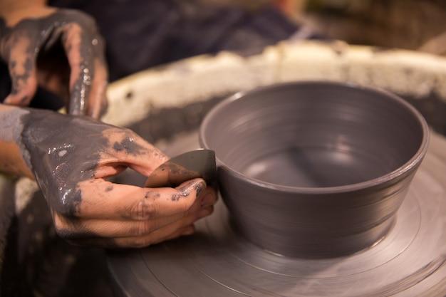 Damskie dłonie w pracy na kole garncarskim z czarnej gliny