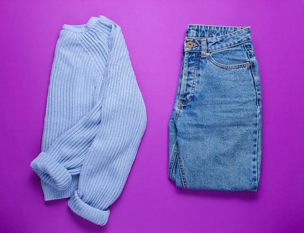 Damskie jeansy i sweter na fioletowym tle