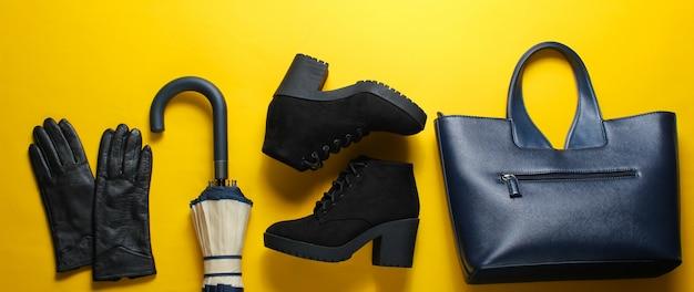 Damskie jesienne buty i dodatki na żółtej powierzchni.