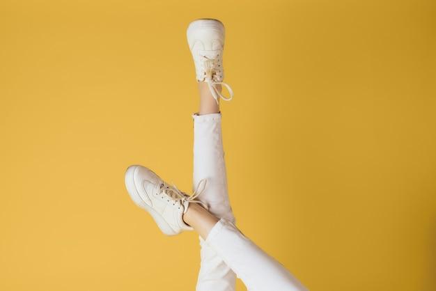 Damskie nogi białe spodnie trampki modne ciuchy luksusowe w stylu ulicznym żółte tło