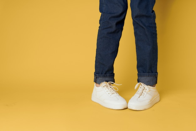 Damskie nogi jeansowe białe trampki moda street style żółty