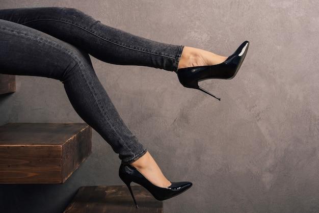 Damskie nogi w dżinsach i butach na wysokim obcasie na drewnianej drabince wspornikowej