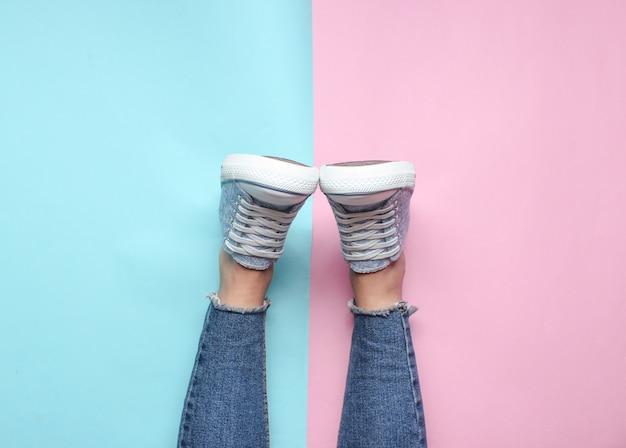 Damskie nogi w obcisłych, podartych dżinsach, tenisówkach na różowym niebieskim pastelowym kolorze. widok z góry