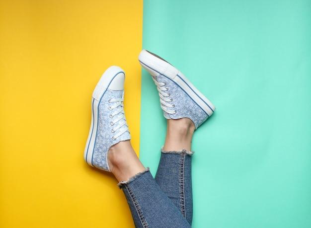 Damskie nogi w obcisłych, podartych dżinsach, tenisówkach na żółto-niebieskim pastelowym kolorze. widok z góry