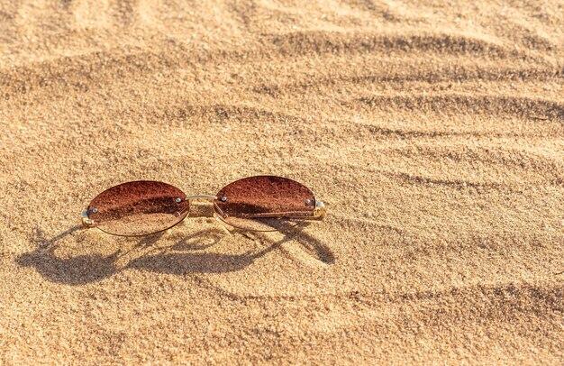 Damskie okulary przeciwsłoneczne bez tytułu na piasku z miejscem na tekst, widok z góry. podróż nad morze. zbliżenie.