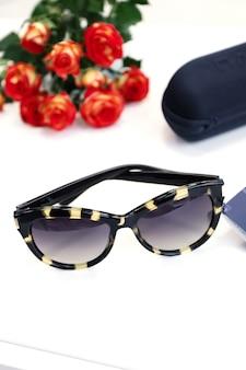 Damskie okulary przeciwsłoneczne na białym tle z różami i skrzynką. sklep z optyką, chroń oczy przed światłem uv.