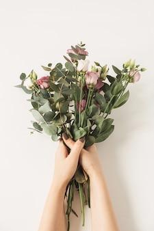 Damskie ręce trzymając bukiet kwiatów róż na białej ścianie