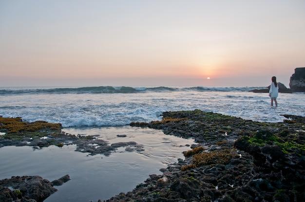 Damy pozycja przy zmierzch sceną przy tanah udziału plażą w bali indonezja