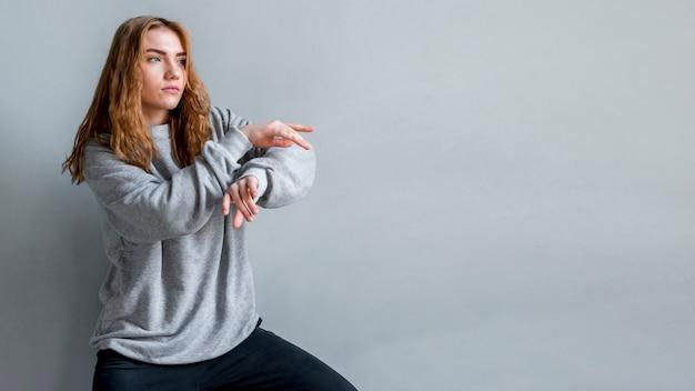 Dancingowa młoda kobieta przeciw szarej ścianie
