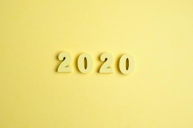 Dane z drewna 2020 na żółtym tle. koncepcja roku. widok z góry.