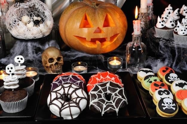 Dania z glazurowanymi pączkami, muffinki ze szkieletami, ciasteczka z marcepanem na halloweenowym stole