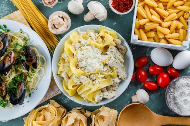 Dania z makaronu w talerzach z surowym makaronem, pomidorem, mąką, grzybami, jajkami, przyprawami, łyżką