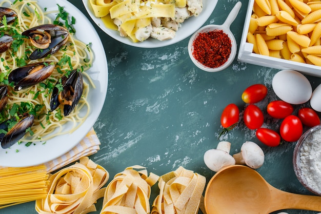 Dania z makaronu z surowym makaronem, pomidorem, mąką, grzybami, jajkami, przyprawami, łyżką w talerzach