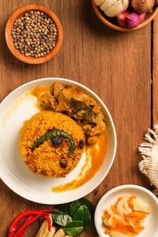 Danie biryani indyjskiej baraniny serwowane na drewnianym stole. typowe jedzenie z indii, zrobione z mięsa koziego zmieszanego z przyprawami i ryżem basmati