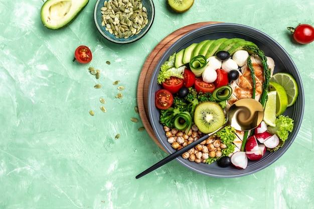 Danie buddha bowl z filetem z kurczaka, szparagami, ciecierzycą, brokułami, rzodkiewką, ogórkiem, awokado, pomidorami, mozzarellą. koncepcja miski detox i zdrowej superfoods, widok z góry, płaskie lay