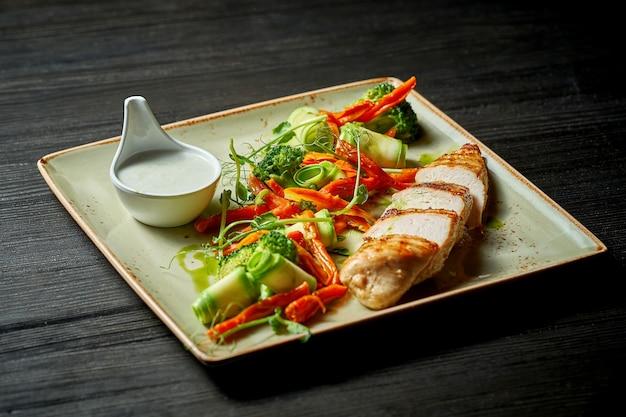 Danie dietetyczne - grillowana pierś z kurczaka z warzywami na parze na drewnianym stole. selektywne skupienie