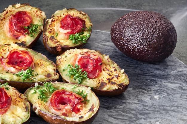 Danie dietetyczne keto: łódki awokado z chrupiącym boczkiem, serem i kiełkami rzeżuchy na szarym kamieniu