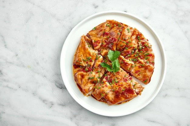 Danie kuchni meksykańskiej - tostada z łososiem, sosem słodko-kwaśnym, cebulą, kolendrą, podawane w białym talerzu na marmurowym stole. zamknij się, selektywna ostrość