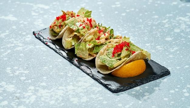 Danie meksykańskie - tacos z łososiem, sałatą, białym sosem i kawiorem tobiko na czarnym talerzu na niebieskiej powierzchni