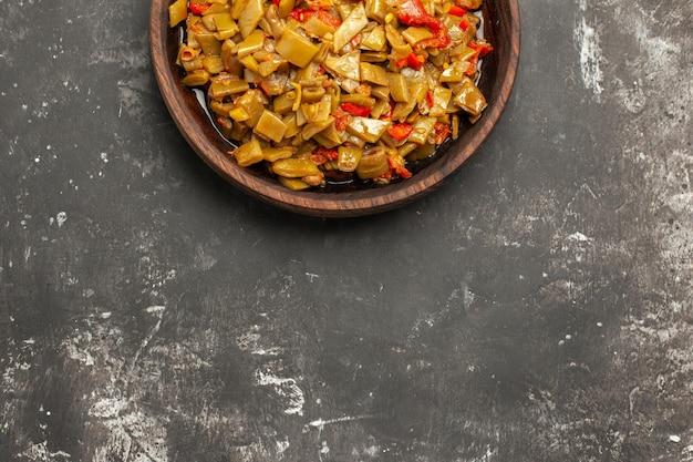 Danie na stole drewniany talerz z apetyczną fasolką szparagową na ciemnym stole